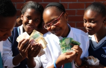 Sisipho (center) and her friends show how much money they've made selling sandwiches.