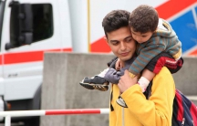 """Ahmed and his family came to Munich from Syria. He is carrying his young cousin.  He came to Germany """"for studying, good work, and to get married and have a baby from [a] German."""""""