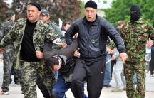 Ukraine pro-Russian rebels carry prisoner in Donetsk