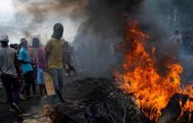 Protesters stand at a burning barricade in the Musaga neighborhood of Bujumbura, Burundi, on May 5, 2015.
