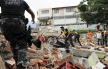 Red Cross members, military and police officers work at a collapsed area after an earthquake struck off Ecuador's Pacific coast, at Tarqui neighborhood in Manta on April 17, 2016.