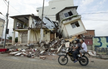 Men ride a motorcycle past damaged buildings in Pedernales after an earthquake struck off Ecuador's Pacific coast.