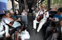 Jorge Luis Jimenez plays the guitar for passengers on a public bus in San Juan, Puerto Rico, on Dec. 2, 2015
