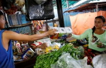 A boy gives a packet of toilet paper, that is made in Colombia, to a customer at a stall that sells staple items and food at a market in La Fria, Venezuela, June 2, 2016.