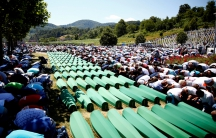 Muslim men pray in front of coffins during mass funeral in Potocari near Srebrenica, Bosnia and Herzegovina on July 11, 2016.