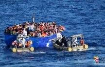 Migrants sit in their boat during a rescue operation by Italian navy ship Borsini (unseen) off the coast of Sicily, Italy, in this handout picture courtesy of the Italian Marina Militare released on July 19, 2016.