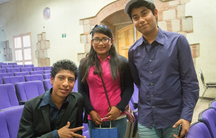 Three teens between a row of purple auditorium chairs