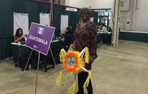 """A woman stands in conference area in front of """"Guatemala"""" sign"""