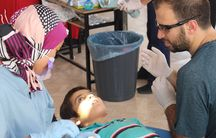"""Whether to say """"needle"""" or """"sleepy juice"""": Dr. Sarah Aref and Farris Barakat help a Syrian boy at the temporary Syrian American Medical Society dental clinic on the Turkish-Syrian border."""
