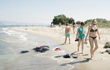 Tourists walk past life preservers on the beaches of Kos, Greece.