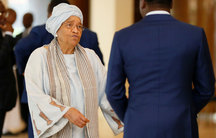 Ellen Sirleaf wears a grey headwrap and robe as she speaks to a man in a blue suit.