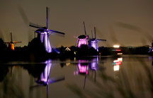 Three lighthouses line a waterway and are lit up purple and pink