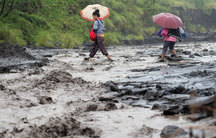 Two women hold pink and orange umbrellas as they carefully walk through a flooded area of dark earth, which is dark with volcanic ash.