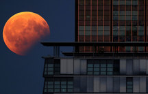 The moon is red-orange as it hangs in the sky next to the left of a high-rise building.