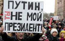 A man holds a white sign with lettering in Russian. He is surrounded by dozens of others. The sign says