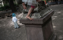 A pupil at the Sophienkirche day-care climbs atop a gravestone in the centers playground. The children are encouraged to explore the space, and not discouraged from climbing on some of the stones.