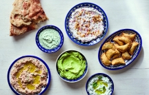 Dips and Small Bites from The Palestinian Table: (clockwise from left) Taboon Bread; Parsley or Cilantro (Coriander) Tahini Spread; Walnut and Garlic Labaneh; Deep-Fried Cheese and Za'atar Parcels; Garlic and Cucumber Labaneh; Avocado, Labaneh, and Preser