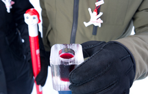A Quebec City carnival-goer warms up with a cold one – Caribou on ice.  Quebec consumes up to 5,000 cases of Caribou yearly, nearly all of it during the winter carnival, and most of that outdoors.