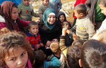 Children crowd around Zein in a camp in southern Aleppo.