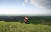 A girl reads on a hill in Glastonbury, England.