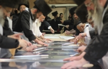 Men lined up in a human assembly line, preparing matzah at the Belz synagogue in Jerusalem.