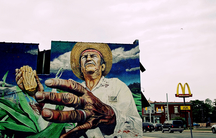 A mural of a farmer on a building, with a McDonald's in the background