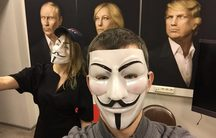 Two people in masks in front of three portraits of Putin, Le Pen and Trump