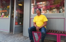 Man sitting on bench in front of sweets shop, looking off camera