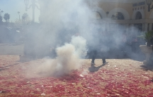 Smoke in front of a man, with remnants of firecrackers on the ground
