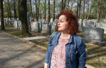 Karen Aroesty standing in front of the headstones of Chesed Shel Emeth cemetery