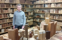 A German scientist stands in front of shelves of wood samples
