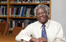 Calestous Juma poses at a table in a portrait photo. Behind him, shelves are lined with books. He has a blue tie and glasses.
