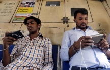 Commuters watch videos on their mobile phones