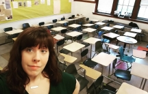 Teacher Suzanne Sutton takes a selfie in front of rows of empty desks at her classroom.
