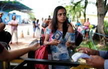 A Venezuelan woman shows her passport and identity card at the Pacaraima border control, Roraima state, Brazil, November 16, 2017.