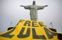 Supporters of former Brazilian President Luiz Inacio Lula da Silva display a banner in front of the statue of Christ the Redeemer in Rio de Janeiro