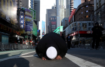 A Muslim man kneels on Broadway Ave. as he takes part in afternoon prayers during an