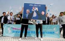 Students hold posters with pictures of South Korea's President Moon Jae-in and North Korea's leader Kim Jong Un