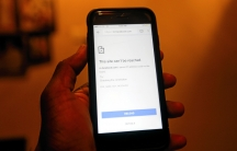 A hand holds a mobile phone with a Facebook logo and the message