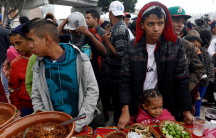 Members of a caravan of migrants from Central America line up to receive food near the San Ysidro checkpoint as the first fellow migrants entered US territory to seek asylum on Monday, in Tijuana, Mexico, April 30, 2018.