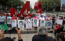 Relatives pose with images of some of the 43 missing Ayotzinapa College Raul Isidro Burgos students in Mexico City.