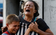 Relatives of inmates held at the General Command of the Carabobo Police react as they wait outside the prison, where a fire occurred in the cells area, according to local media, in Valencia, Venezuela, March 28, 2018.
