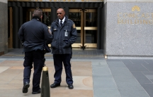 A police officer and security official stand outside 30 Rockefeller Plaza.