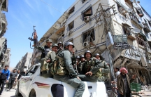 Syrian police hold weapons while they ride in the bed of a pickup truck in Doma.