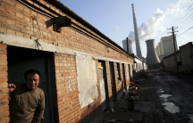 A man leans out of the door of his house down the street from large coal power plant smokestacks in Beijing.