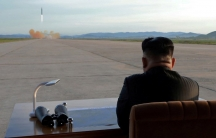 North Korean leader Kim Jong-un sits at a desk in the nearground and watches a missile launch in the distance.
