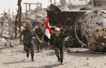 Soldiers loyal to Syria's President Bashar al-Assad are seen running toward the camera with one carrying the Sryian flag.