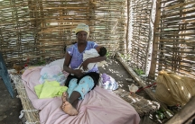 Christella Saintime sits with her 6-week-old baby, several feet from the Dominican Republic. She fled to Haiti when she was 5 months pregnant.