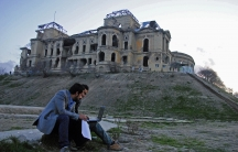 Youngsters surf the Internet near the ruined Darul Aman Palace, which was built in the 1930s. Only 5.5 percent of Afghan youths have access to the Internet, but technology played a role in connecting youth during last year's presidential elections.