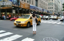A woman hails a cab outside the Empire State Building in New York City.